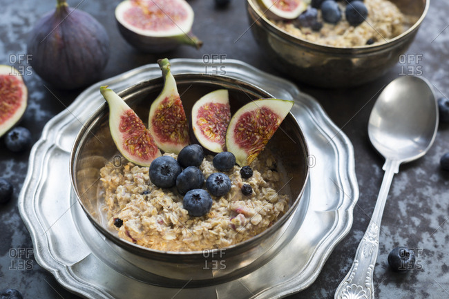 Bowl of porridge with sliced fig- blueberries and dried berries