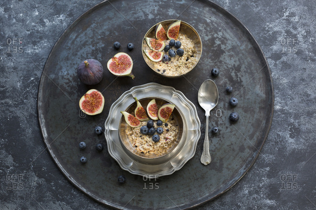 Bowls of porridge with sliced figs- blueberries and dried berries