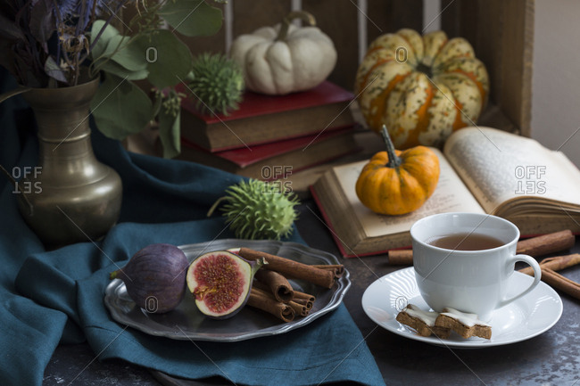 Autumnal still life with figs- cinnamon sticks- books and a cup of tea