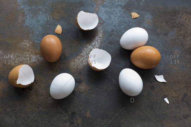 White and brown eggs and eggshells on rusty metal