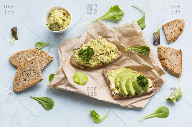 Slices of bread with sliced avocado and avocado cream on brown paper