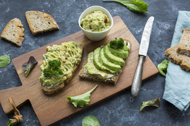Slices of bread with sliced avocado and avocado cream on wooden board