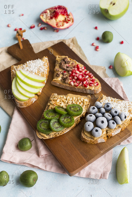 Bread slices with various toppings on wooden board