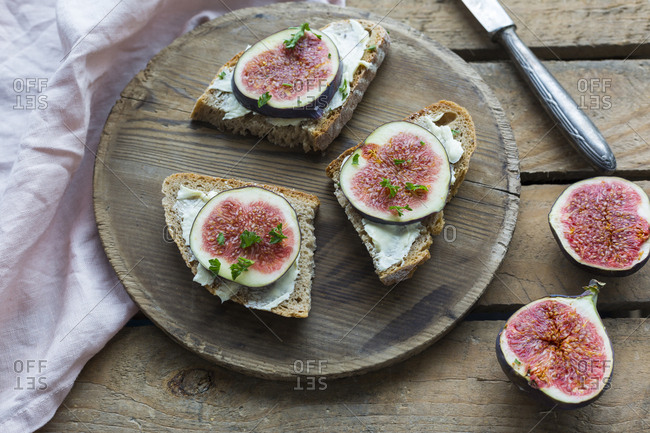 Buttered slices of bread with sliced figs on wooden plate