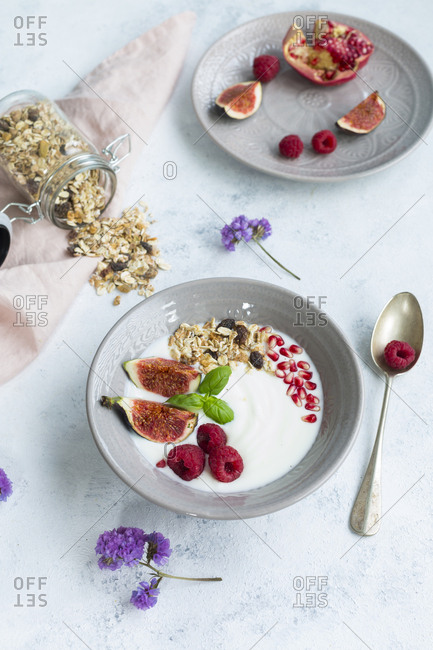 Bowl of natural yoghurt with fruit muesli- raspberries- figs and pomegranate seed