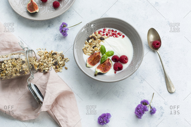 Bowl of natural yoghurt with fruit muesli- raspberries- figs and pomegranate seeds