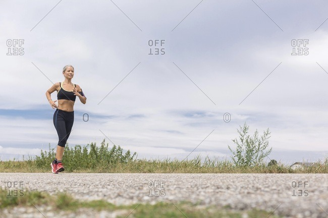 Mature woman running on remote country lane in summer