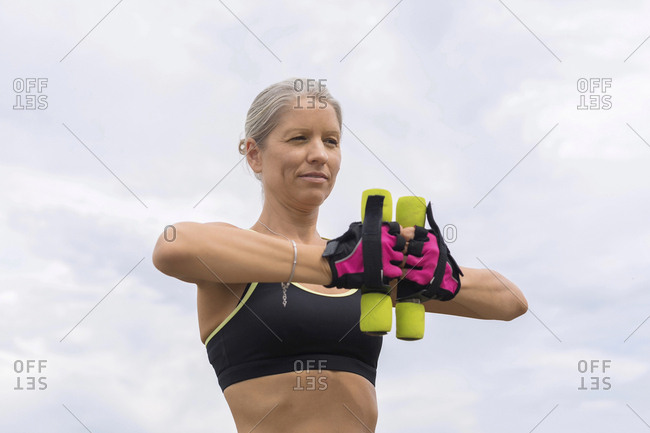 Mature woman doing workout with dumbbells outdoors