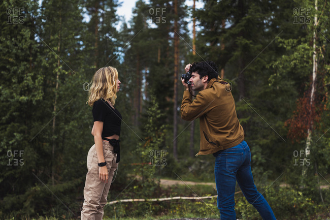 Finland- Lapland- man taking picture of woman in rural landscape