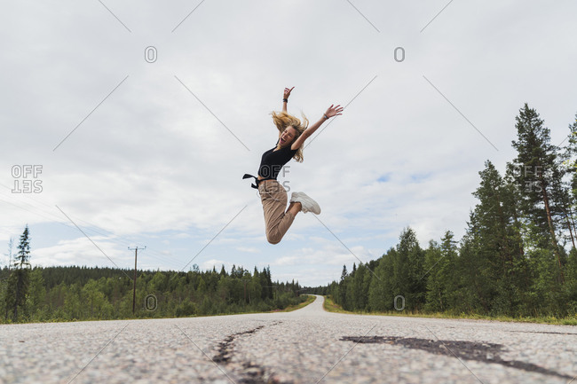 Finland- Lapland- exuberant young woman jumping in rural landscape
