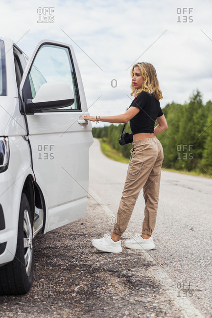 Finland- Lapland- young woman at country road getting into a car
