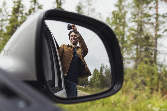Finland- Lapland- wing mirror reflection of man taking picture out of a car