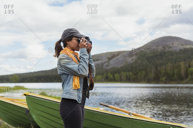 Finland- Lapland- woman taking picture with a camera at the lakeside