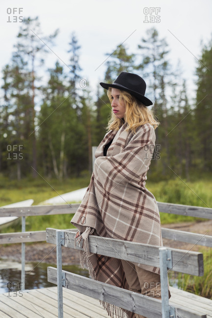 Finland- Lapland- woman wearing a hat wrapped in a blanket standing on jetty at the lakeside