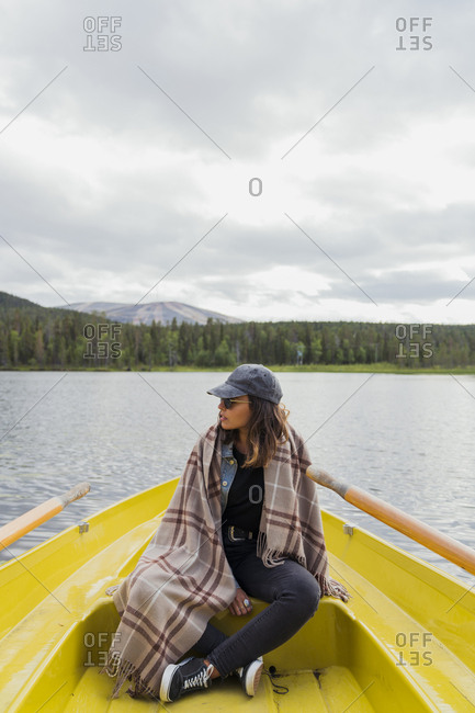 Finland- Lapland- woman wearing a blanket on a boat on a lake
