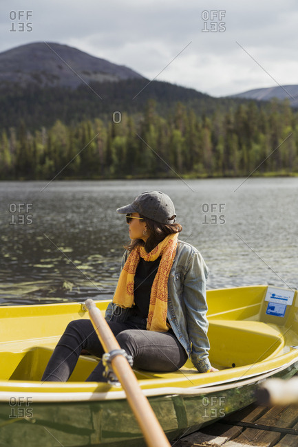 Finland- Lapland- woman sitting in a boat on a lake