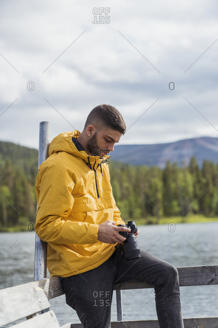 Finland- Lapland- young man with a camera on jetty at a lake