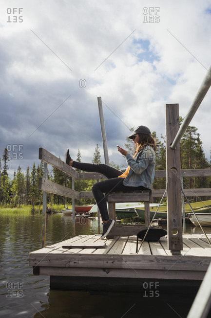 Finland- Lapland- woman sitting on jetty at a lake using cell phone