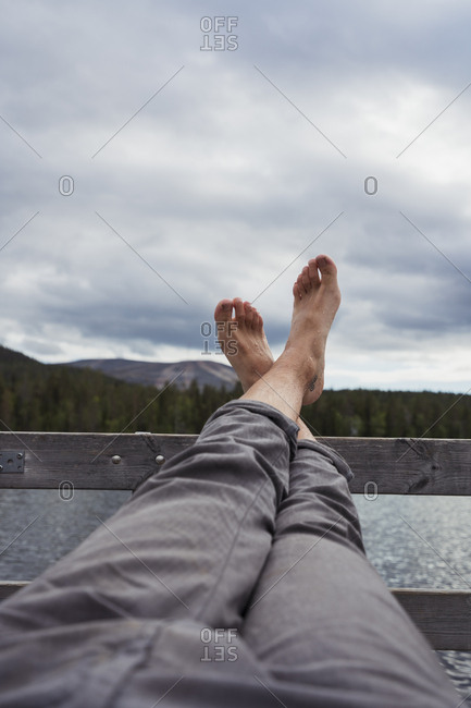 Man sitting on jetty at a lake holding his feet up