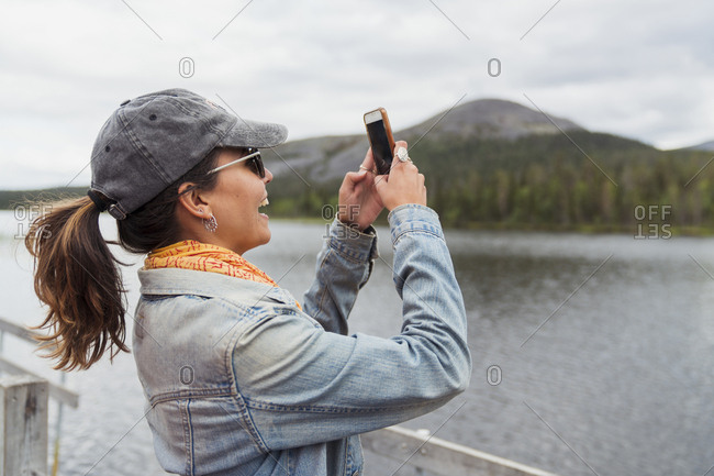 Finland- Lapland- happy woman on jetty at a lake taking a selfie