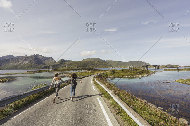 Young women walking on an empty road- Lapland- Norway