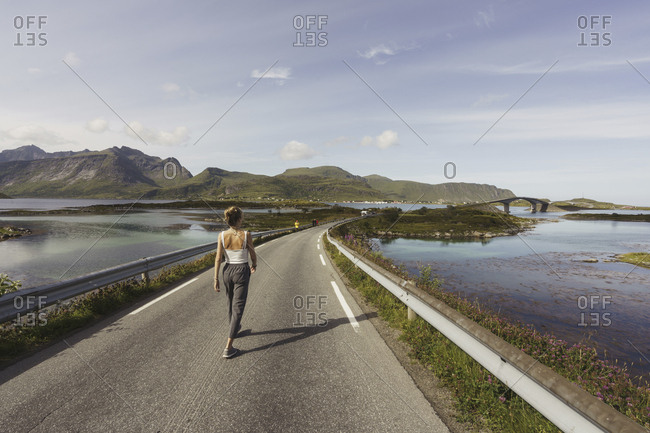 Young woman walking on an empty road- Lapland- Norway