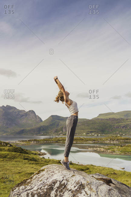 Young woman standing in nature- stretching- Lapland- Norway