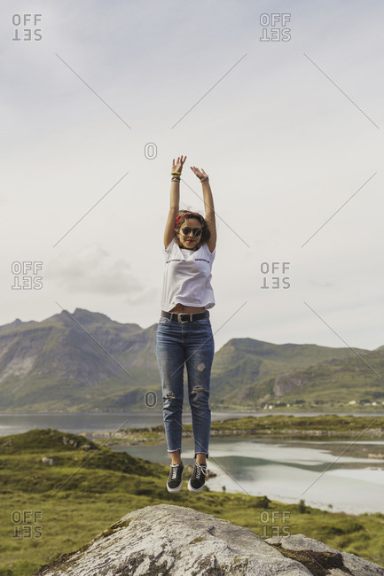 Young woman jumping on a rock- Lapland- Norway