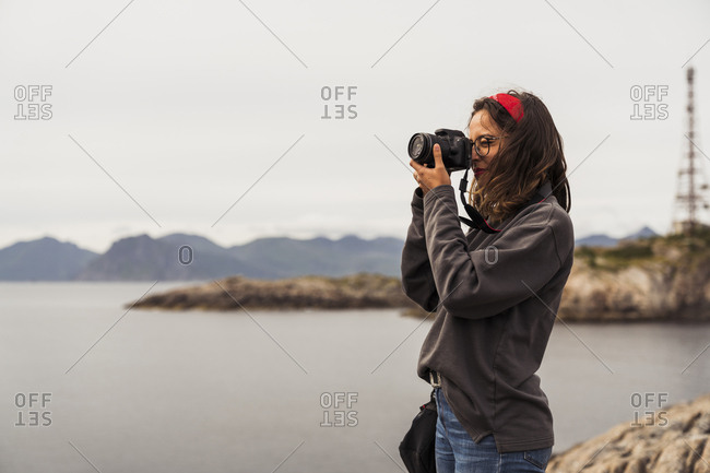 Young woman taking pictures of a lake in Vesteralen Island- Lapland- Norway