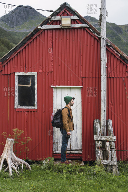 Young man standing in front of corrugated iron shack