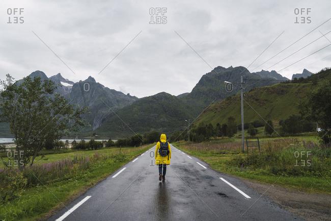 Norway- Lapland- Vesteralen Islands- Young man walking on empty road- rear view