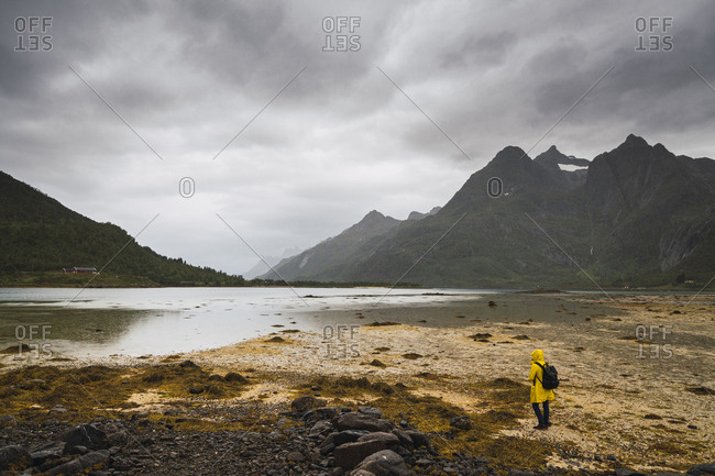 Young man standing at a lake in Vesteralen Island- Lapland- Norway