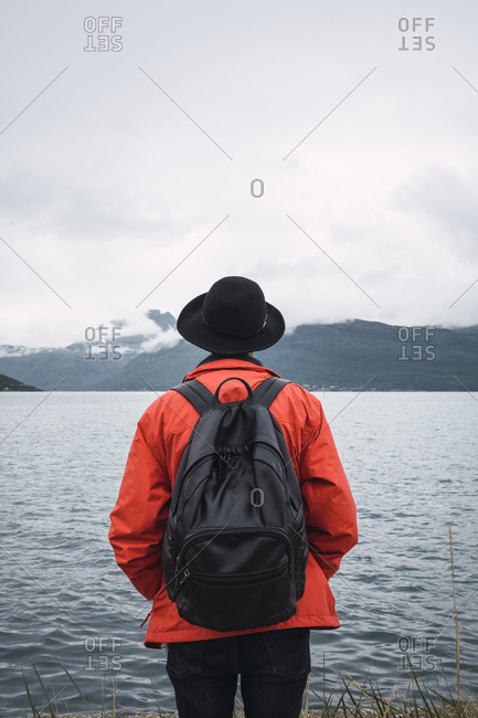 Young man standing by water- looking at distance- rear view