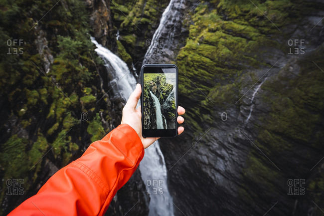 Person taking smartphone picture of a waterfall- Lapland- Norway