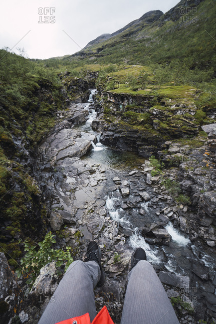 Person sitting at a brook- Lapland- Norway