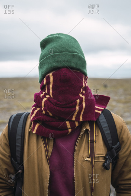 Young man with woolly hat and scarf- wrapped around face