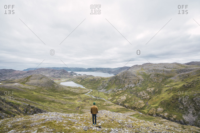 Finland- Lapland- man standing on a hill in stunning landscape