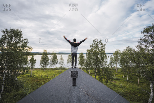 Finland- Lapland- man standing on roof of a house at a lake with raised arms