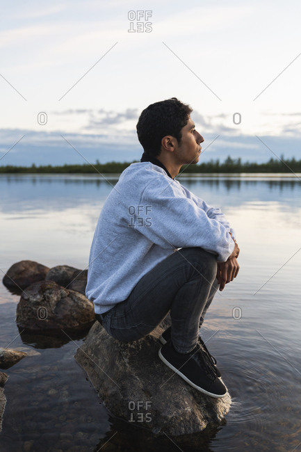 Finland- Lapland- man sitting on a rock in a lake