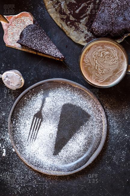 Imprint of a slice of cake and a fork- made with powdered sugar- mug of coffee- chocolate cake