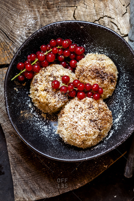 Plum filled sweet dumplings with coconut-cinnamon crust and redcurrants