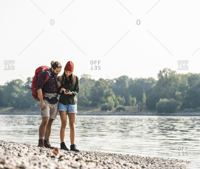 Young couple with backpacks at the riverside checking cell phone
