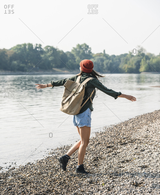 Carefree young woman walking at the riverside