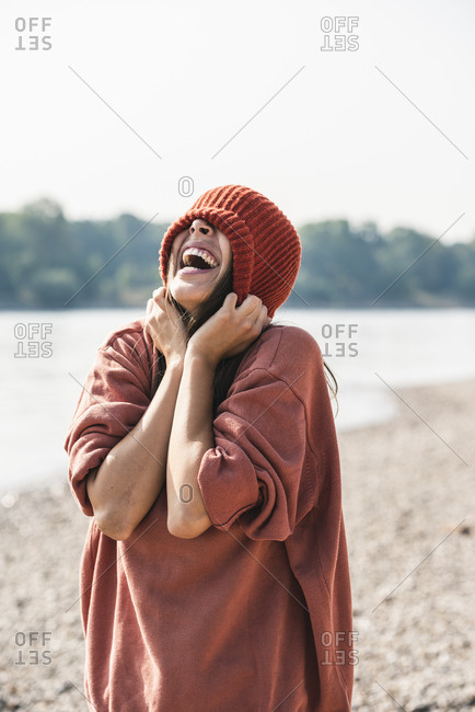 Carefree young woman wearing wooly hat at the riverside