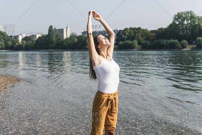 Happy young woman standing relaxed at the riverside