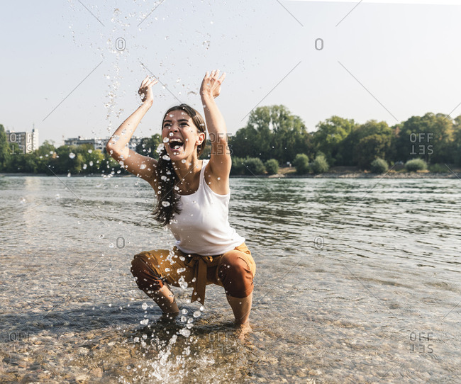 Carefree young woman refreshing in water of a river