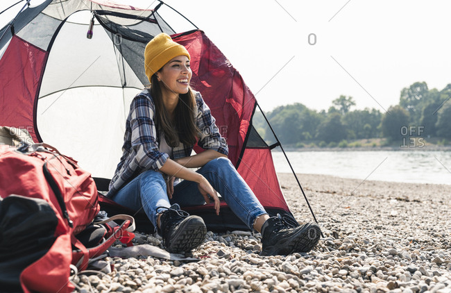 Happy young woman sitting at a tent at the riverside