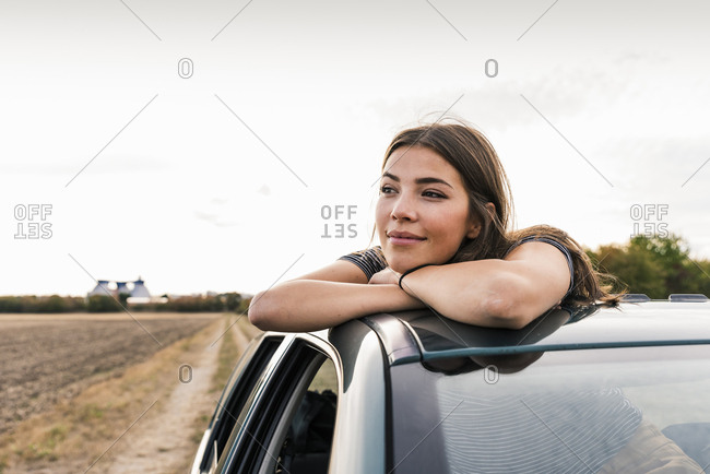 Smiling young woman looking out of sunroof of a car