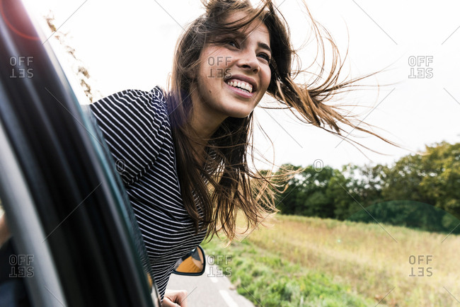 Happy young woman leaning out of car window