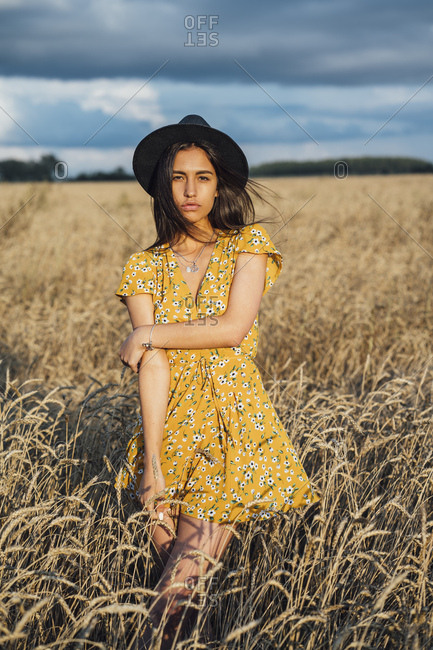 Portrait of young woman wearing summer dress with floral design and a hat dancing in corn field